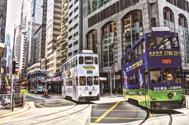 <br />  (撮影)Headline編集長 中野 哲也 PENTAX K-S2使用 <br />   (【尾灯】写真) RICOH Quarterly HeadLine Vol.15 2017春 <br /> <br />  東京やニューヨークはどんなに歩いても飽きない都市。その仲間に香港も付け加えてもよいだろう。飽きない=商いでもあり、アジアを代表する株式市場は早朝から世界中のマネーを吸い上げる。トレーダーは最先端のテクノロジーを駆使しながら、パソコン上で超高速取引を繰り返す。その一方で、100年超の歴史を持つ「庶民の足」を大事にするのも香港らしい。その二階建てトラム(路面電車)は高層ビルの間を縫うように走る。一戸数億円のタワーマンションが立ち並んでも、数十円の初乗り運賃を守るトラムは香港の経済的格差の象徴であり、社会的安定を守る知恵でもある。夜が更けてトラムに乗り、ヴィクトリア・ピークに登ると、眼下に広がるのは…。おもちゃ箱みたいな街だから、飽きないのだろう。(N)